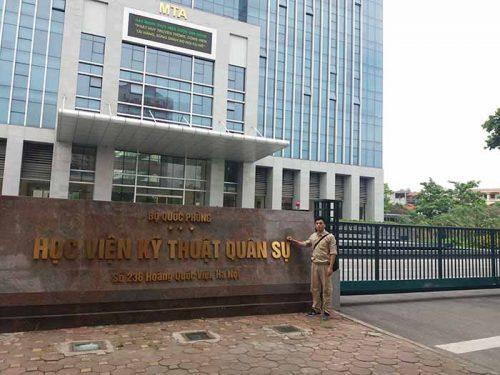 Nhân viên công ty bên cạnh bảng tên của học viện kỹ thuật quân sự